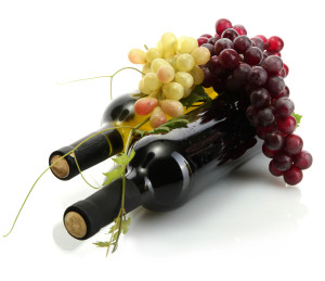 bottles of wine and ripe grapes isolated on white